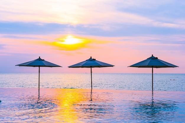 傘と日の出か日没時にスイミングプールの周りの椅子海の海のビーチ