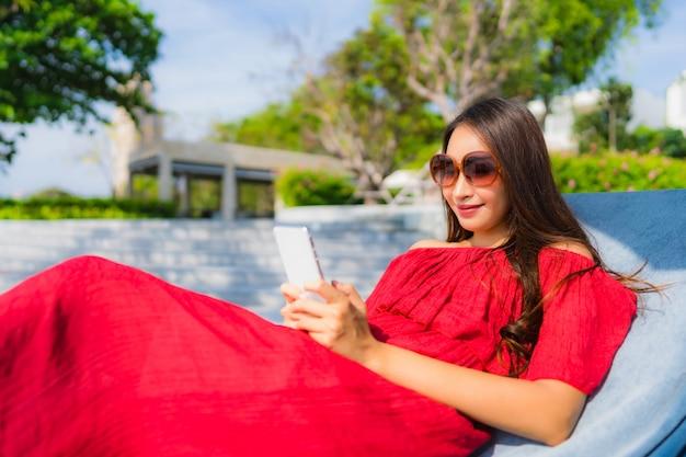 Женщина портрета красивая молодая азиатская с сотовым телефоном или мобильным телефоном вокруг бассейна на курорте гостиницы