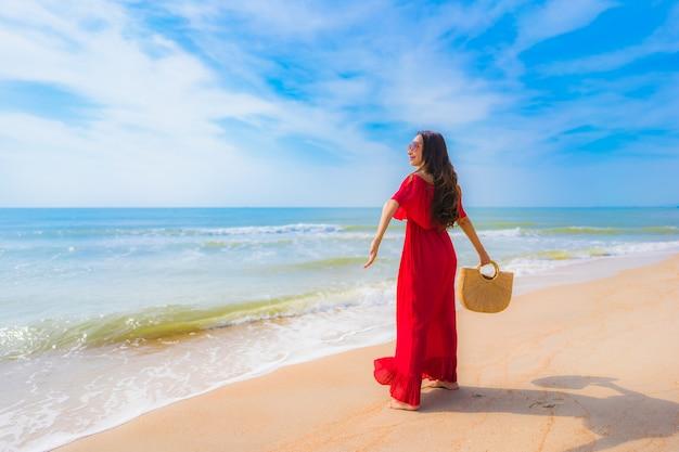 Женщина портрета красивая молодая азиатская на пляже и море