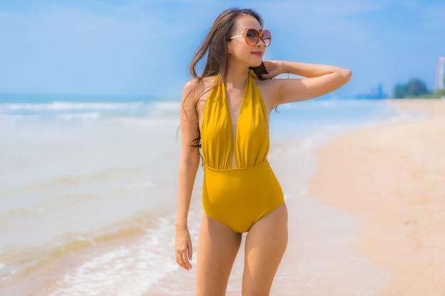Улыбка женщины портрета красивая молодая азиатская счастливая на пляже и море