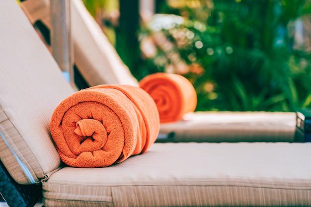 デッキチェアにオレンジのプールタオル