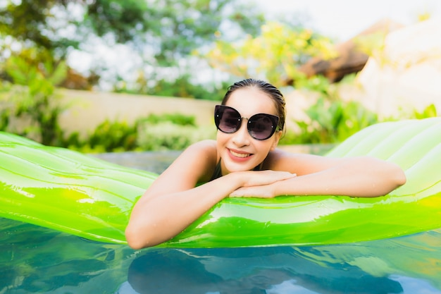 肖像画美しい若いアジア女性笑顔幸せリラックスして、スイミングプールでのレジャー