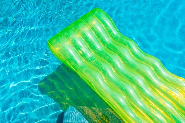 スイミングプールの水の周りにカラフルな水泳リングやゴム製フロート