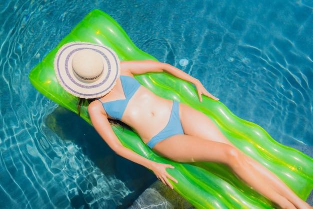 Улыбка женщины портрета красивая молодая азиатская счастливая ослабляет и отдыхает в бассейне