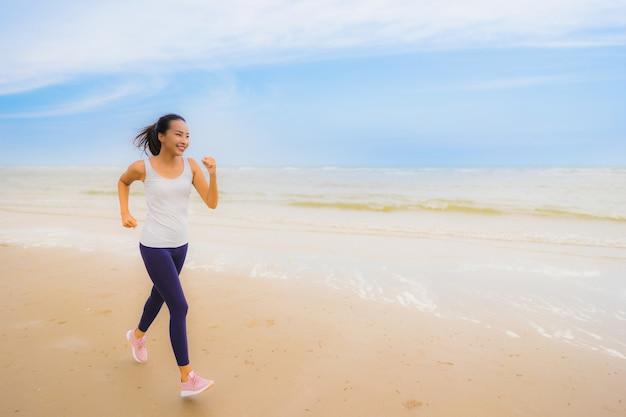 肖像画美しい若いスポーツアジア女性運動と屋外の自然ビーチと海でジョギング運動