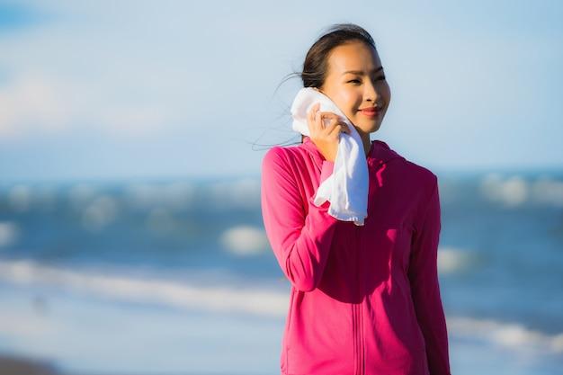 肖像画の美しい若いアジア人女性を実行しているか、ビーチの熱帯の自然風景の運動