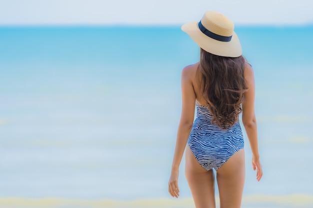 Улыбка красивой молодой азиатской женщины портрета счастливая ослабляет на тропическом океане моря пляжа для путешествия отдыха