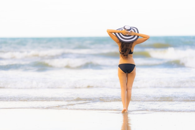 Бикини носки женщины портрета красивое молодое азиатское на океане моря пляжа