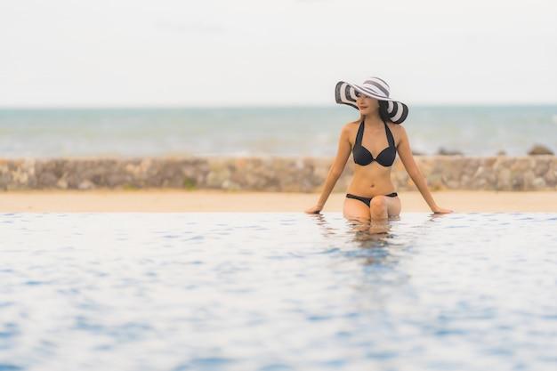 肖像画美しい若いアジア人女性はホテルのリゾート地のスイミングプールの周りビキニを着るほぼ海海ビーチ