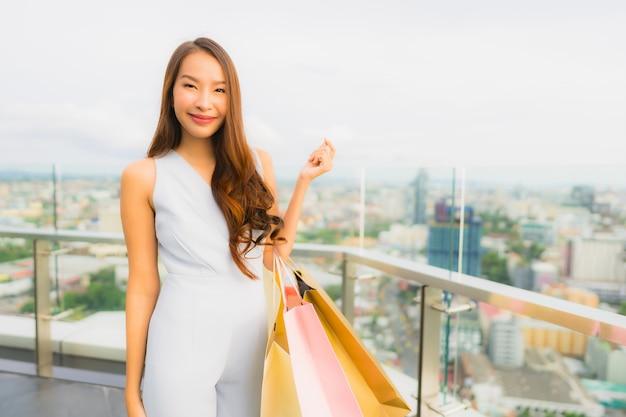 幸せな肖像画美しい若いアジア女性とデパートからの買い物袋と笑顔