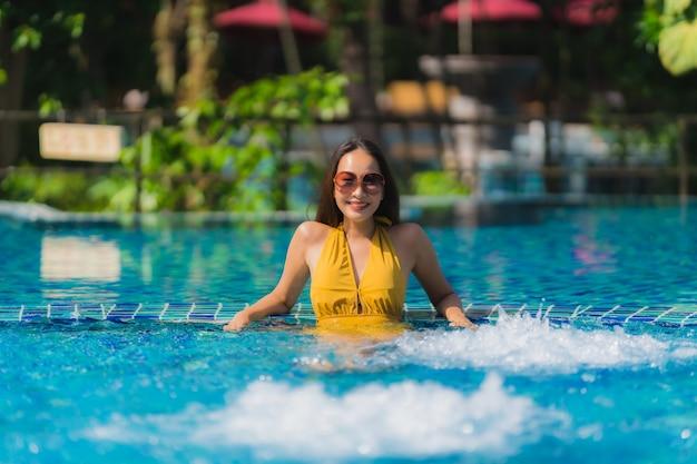 肖像画美しい若いアジア女性レジャーは笑顔とホテルリゾートのプールの周り幸せにリラックス