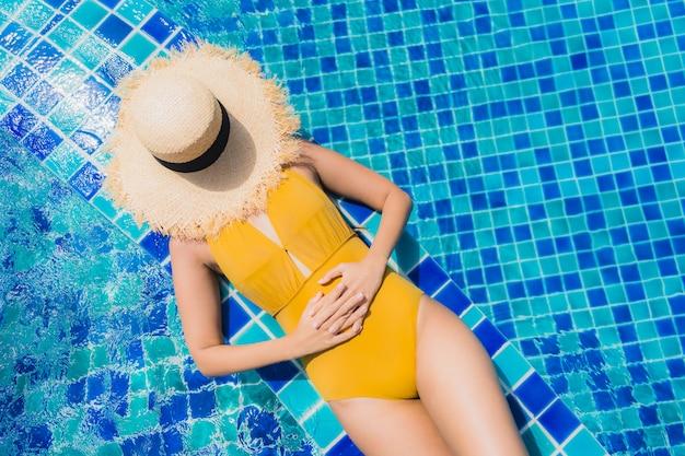 Досуг женщины портрета красивый молодой азиатский ослабляет улыбку и счастливый вокруг бассейна в курорте гостиницы
