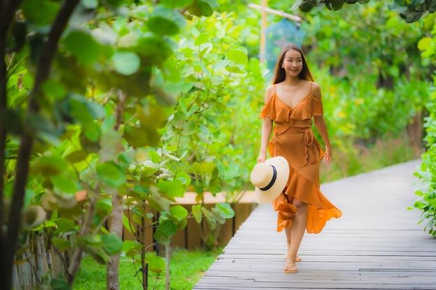 肖像画美しい若いアジア女性は庭の散歩道の上を歩く