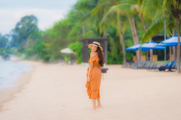 Улыбка красивой молодой азиатской женщины портрета счастливая ослабляет на океане моря пляжа