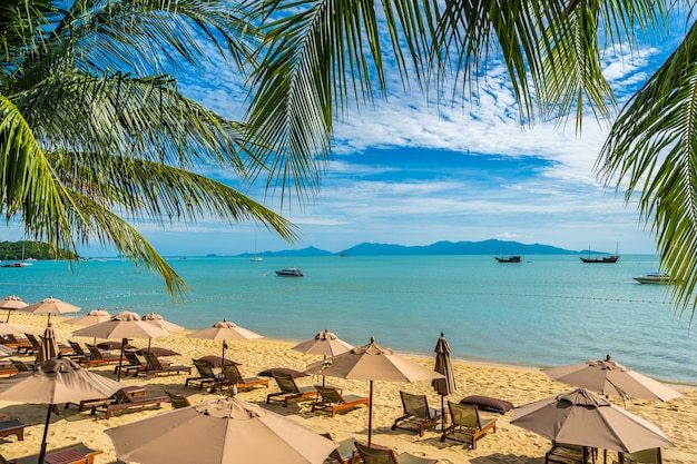 美しい熱帯のビーチ海とヤシの木と傘と青い空に椅子と海
