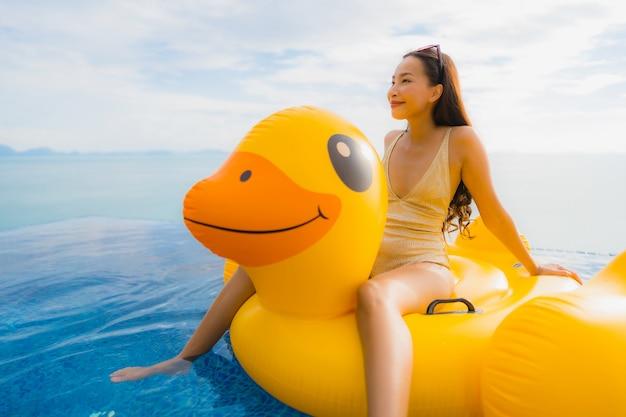 Женщина портрета молодая азиатская на раздувной утке желтого цвета поплавка вокруг открытого бассейна в гостинице и курорте