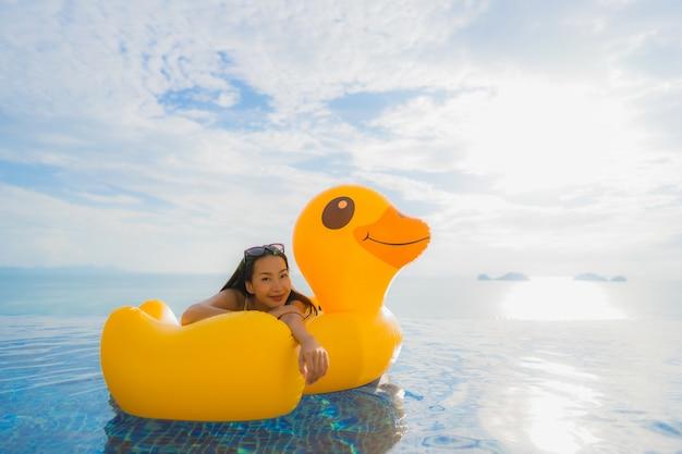 ホテルやリゾートの屋外スイミングプールの周りのインフレータブルフロート黄色アヒルの肖像若いアジア女性