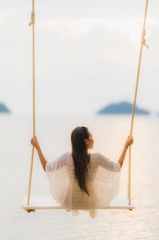 Женщина портрета красивая молодая азиатская сидя на качании вокруг океана моря пляжа для ослабляет