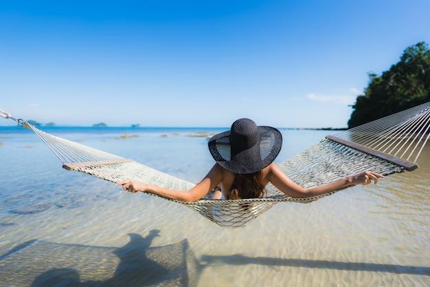 Женщина портрета красивая молодая азиатская сидя на гамаке вокруг океана пляжа моря для ослабляет