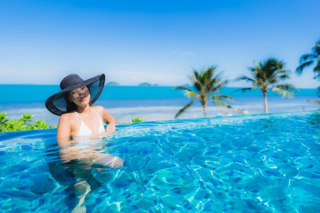 Портрет красивая молодая азиатская женщина расслабиться в роскошном открытом бассейне в отеле курорта почти пляж море океан
