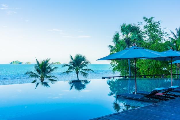 Зонтик и стул вокруг красивого роскошного открытого бассейна с видом на море и море в курортном отеле для отпуска
