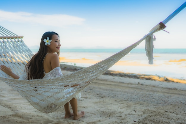 海のビーチの周りのハンモックの上に座っての肖像画美しい若いアジア女性リラックス
