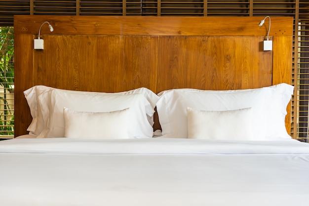ベッドの上の美しい豪華で快適な白い枕と寝室で毛布の装飾