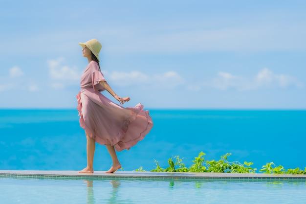 Женщина портрета молодая азиатская ослабляет улыбку счастливую вокруг открытого бассейна в курорте гостиницы с видом на океан моря