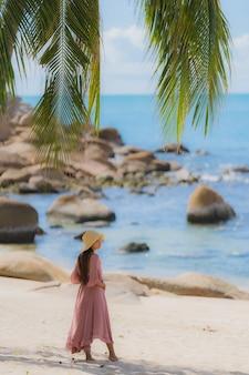 休日の休暇のためのココヤシの木とビーチ海海の周り幸せな肖像画若いアジア女性笑顔