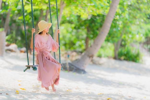 スイングロープとビーチ海オーシャンココナッツ椰子の木の周りの海の上に座って肖像若いアジア女性