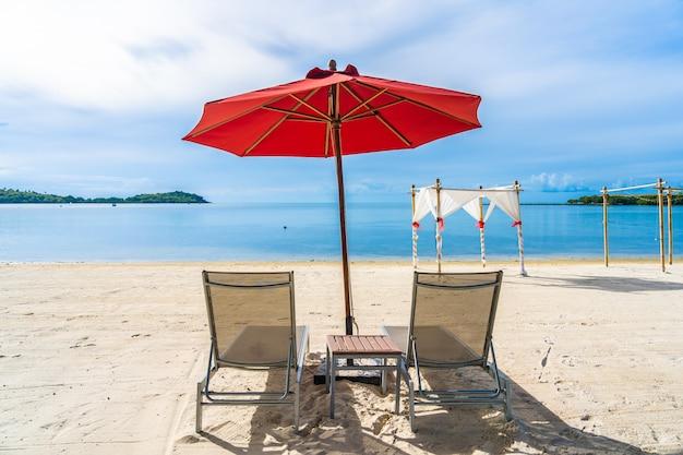 Красивый открытый тропический пляж морской океан с зонтиком стулом и шезлонгом вокруг на белом облаке голубом небе