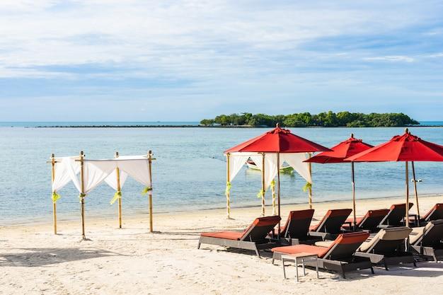 白い雲青い空の上の周りの傘の椅子とラウンジデッキの美しい屋外熱帯ビーチ海