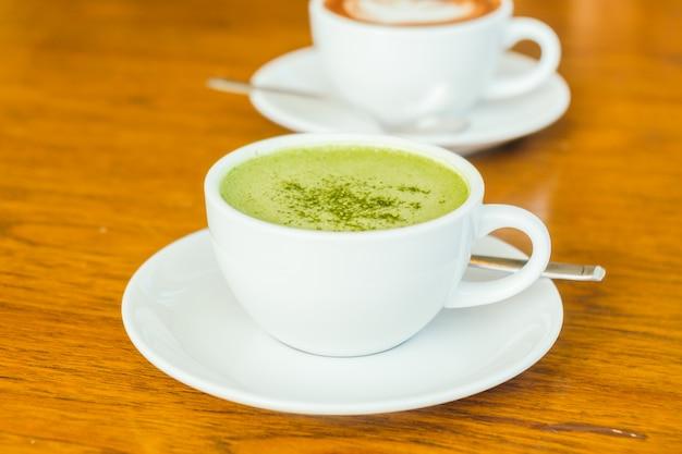 白い杯の緑色の抹茶ラテッティ