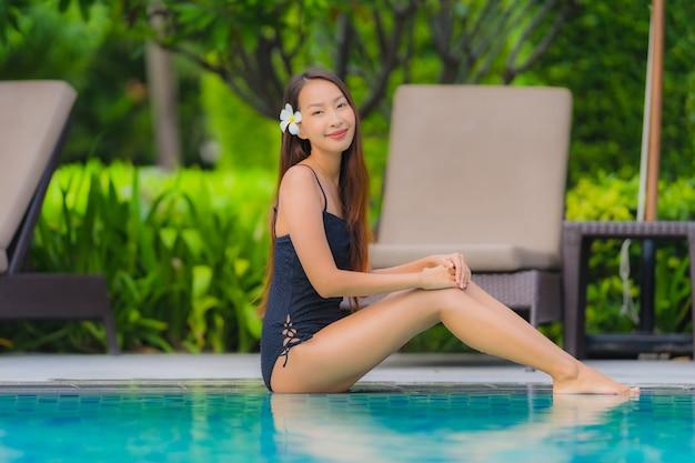 アジアの若い女性の肖像画は、海のオーシャンビューのホテルリゾートの屋外スイミングプールの周り幸せな笑顔をリラックス