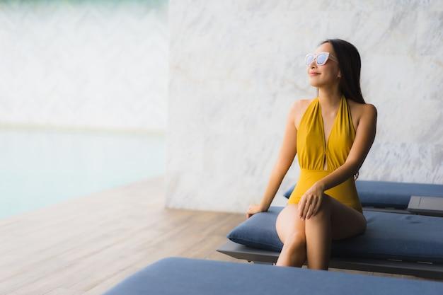 Улыбка азиатской красивой молодой женщины портрета счастливая ослабляет вокруг открытого бассейна в каникулах праздника