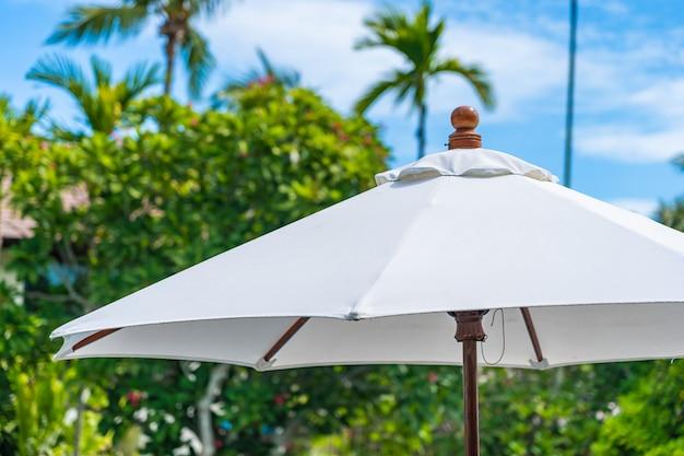 Селективный фокус на зонтик с кокосовой пальмы на фоне для отдыха