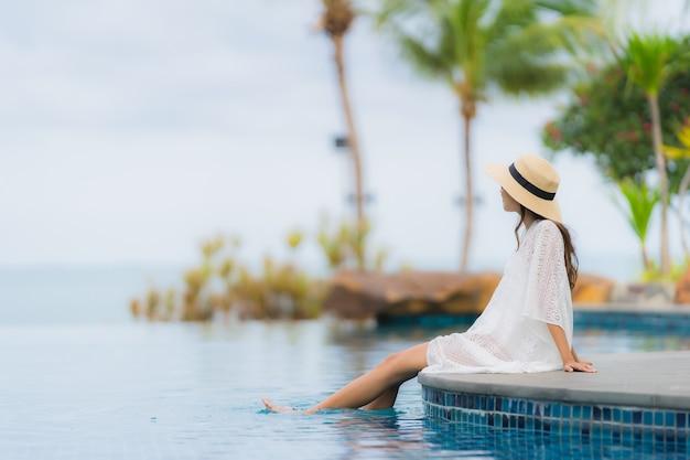 Улыбка женщины портрета красивая молодая азиатская счастливая ослабляет вокруг бассейна в курорте гостиницы