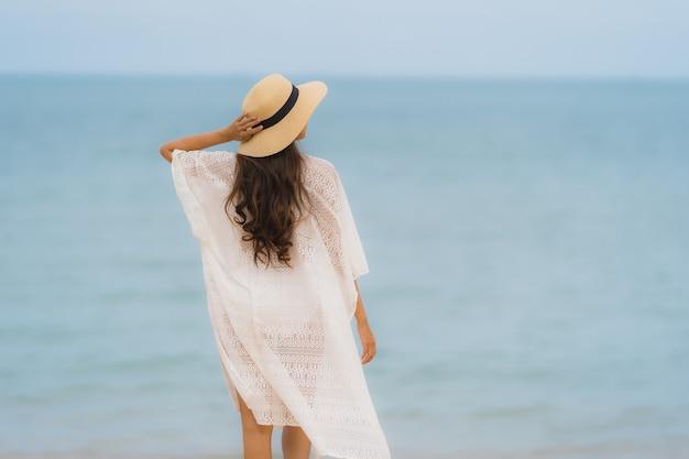 Улыбка женщины портрета красивая молодая азиатская счастливая ослабляет на океане моря пляжа