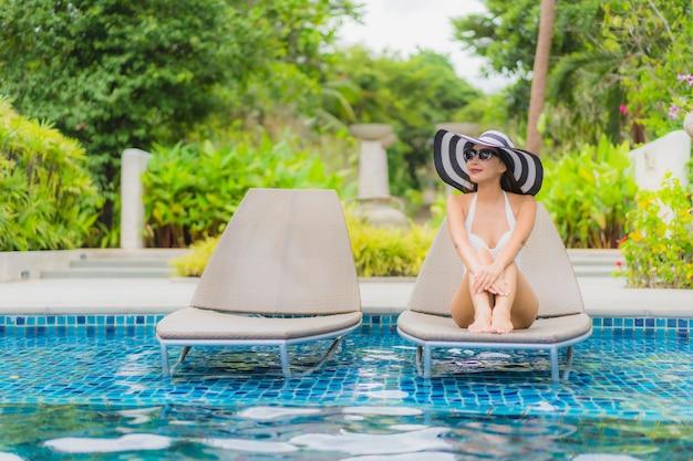 肖像画美しい若いアジア女性笑顔幸せなホテルリゾートのスイミングプールの周りでリラックス