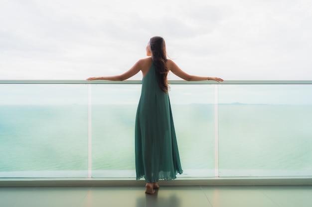 Улыбка красивой азиатской женщины портрета счастливая ослабляет на балконе с океаном моря