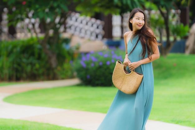 美しい肖像若いアジアの女性の幸せな笑顔は、庭で散歩とリラックスします。