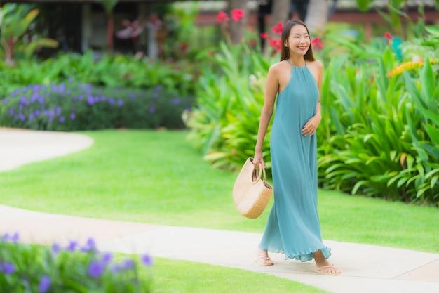 Улыбка красивой азиатской женщины портрета счастливая ослабляет с прогулкой в саде