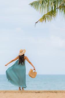 Улыбка красивых азиатских женщин портрета счастливая ослабляет вокруг океана моря пляжа