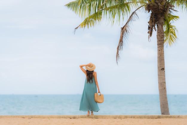 美しいアジアの若い女性の幸せな笑顔は、ビーチ海海の周りでリラックスします。