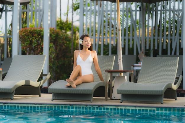 Улыбка молодой азиатской женщины портрета счастливая ослабляет вокруг бассейна в курорте гостиницы