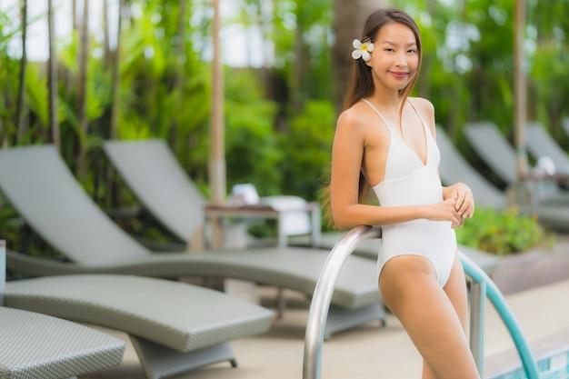 肖像若いアジア女性の幸せな笑顔はホテルリゾートのスイミングプールの周りでリラックスします。