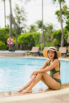 Улыбка красивых азиатских женщин портрета счастливая ослабляет вокруг бассейна в курорте гостиницы