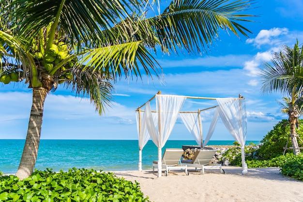 旅行のための青い空とビーチ海海の周りの美しい傘と椅子