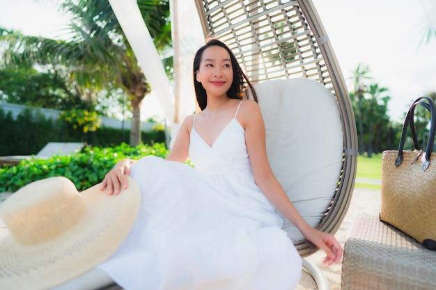 幸せな笑顔でビーチ海海の周りの美しいアジアの女性の肖像画