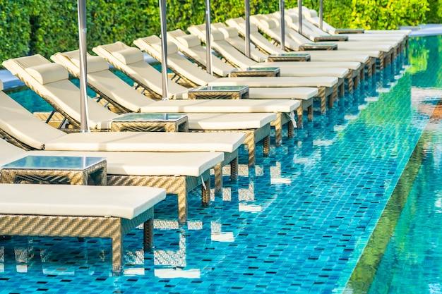 Зонтик и кресло-диван вокруг открытого бассейна на территории курортного отеля для летнего отдыха